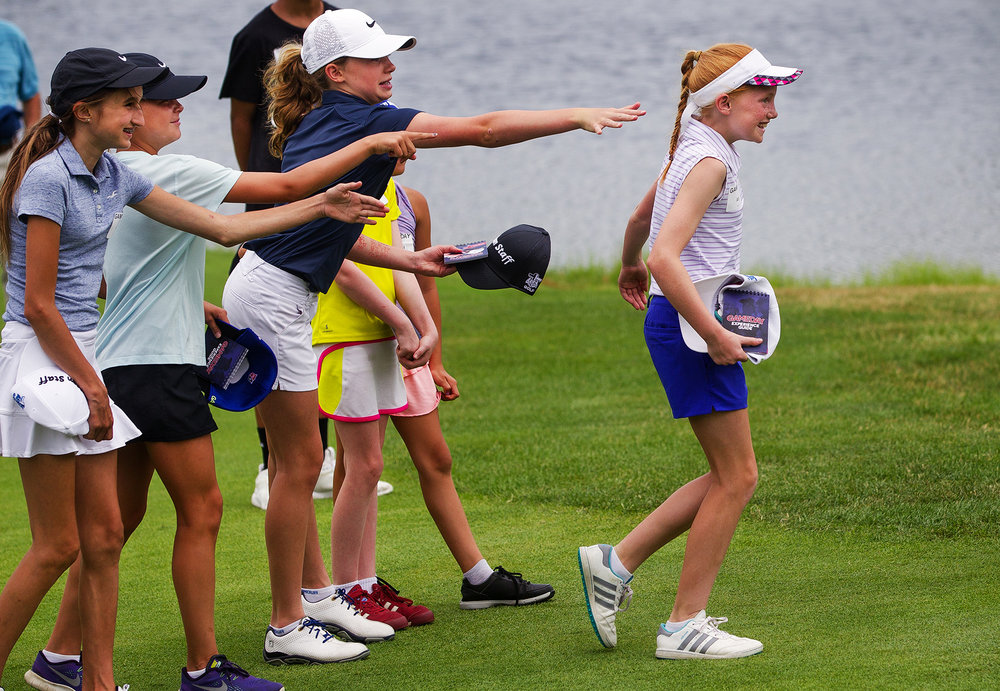 Izzy Hassebrock reluctantly steps forward after her friends gave her a nudge when Jared Wolfe asked for the best female golfer in the group to step forward and help him with a putt during the  Lincoln Land Championship Fellowship of Christian Athletes Golf Gameday clinic, a pre-tourney event at Panther Creek Golf Course Tuesday, June 26, 2018. [Ted Schurter/The State Journal-Register]