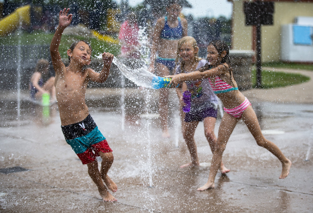 Eli Humke, 8, tries to evade a water attack from Amara Kaeding, 9, as the youth chill out in the fountains of Southwind Park as temperatures reached into the 90s, Thursday, June 28, 2018, in Springfield, Ill. According to the National Weather Service in Lincoln, the Springfield area is under an excessive heat warning for Friday and Saturday with heat index values possibly reaching 113 degrees. [Justin L. Fowler/The State Journal-Register]