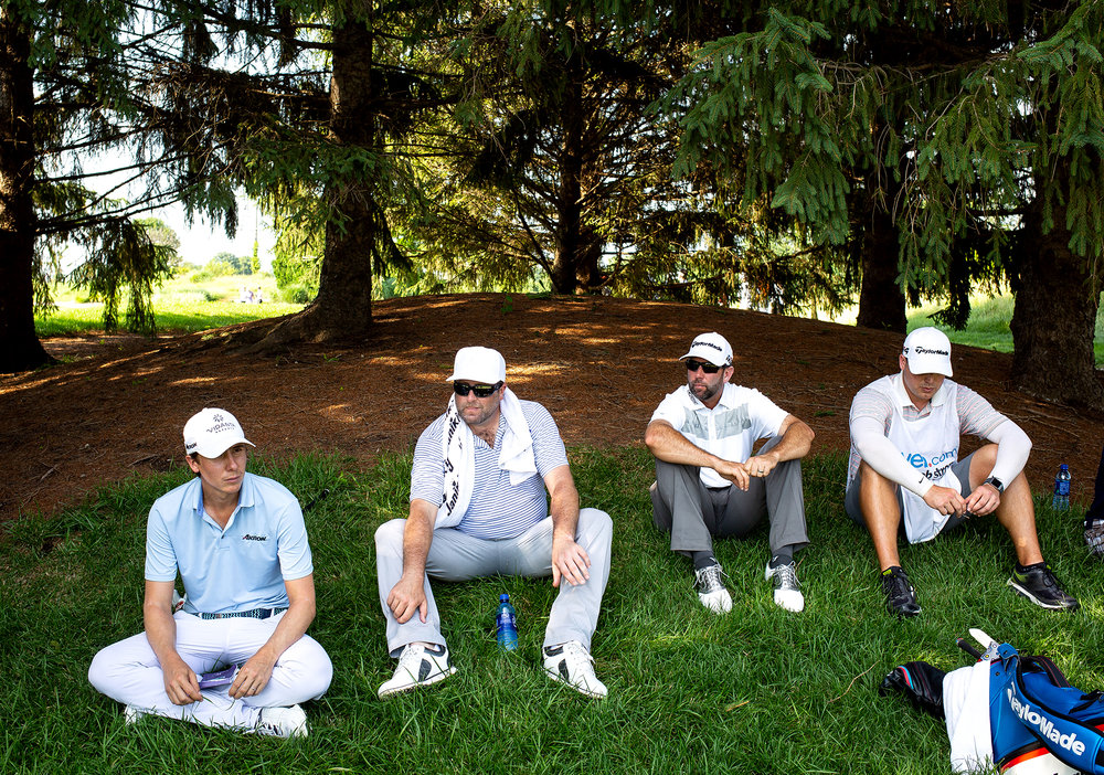 Web.com tour pros Carlos Ortiz, left, Steve Marino, Josh Teater and Lee Chaney, Teater's caddie, take to the shade at the No. 6 tee while they wait for the group ahead of them to clear the fairway during second round play at the Lincoln Land Championship Friday, June 29, 2018 at Panther Creek Country Club in Springfield, Ill. [Rich Saal/The State Journal-Register]