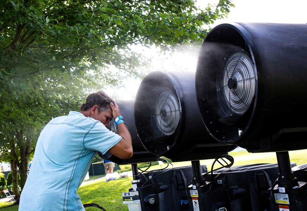 Matt Burns finds cool comfort in front of the mist machines at Panther Creek Country Club where he had been watching the Lincoln Land Championship Friday, June 29, 2018 in Springfield, Ill. [Rich Saal/The State Journal-Register]