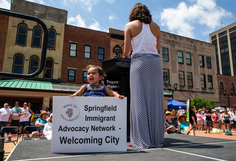 "Eighteen-month-old Elena Pava Cueto, grabs a sign to show off on stage as her mother, Valeria Cueto, tells her story as a first generation American citizen, during the ""Families Belong Together"" rally on the Old State Capitol Plaza, Saturday, June 30, 2018, in Springfield, Ill. [Justin L. Fowler/The State Journal-Register]"