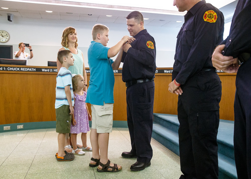 John Gordon has his badged pinned by his son Jacob, 12, as he is joined by his family to receive his promotion to Driver/Engineer during a promotions ceremony for the Springfield Fire Department at the City Council Chambers, Thursday, July 5, 2018, in Springfield, Ill. [Justin L. Fowler/The State Journal-Register]