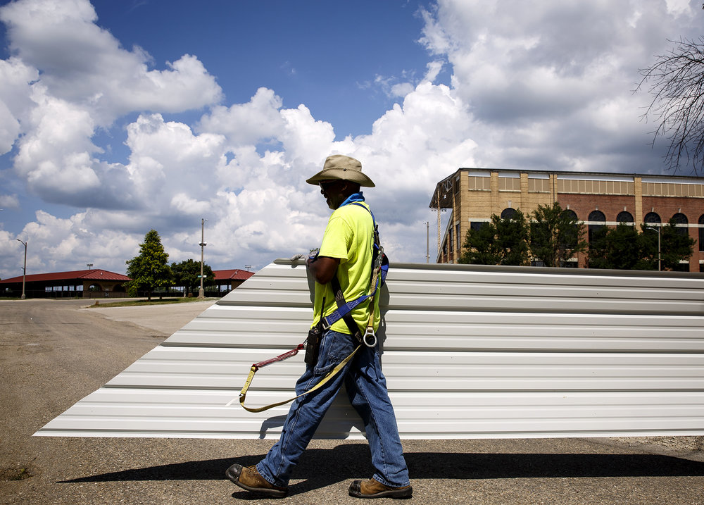 Gaylon Richards carries a piece of corrugated steel sheeting for the new roof of the sheep barn at the state fairgrounds Monday, July 9, 2018 in Springfield, Ill. The roof is one of the improvement projects being made before the State Fair begins in August. [Rich Saal/The State Journal-Register]