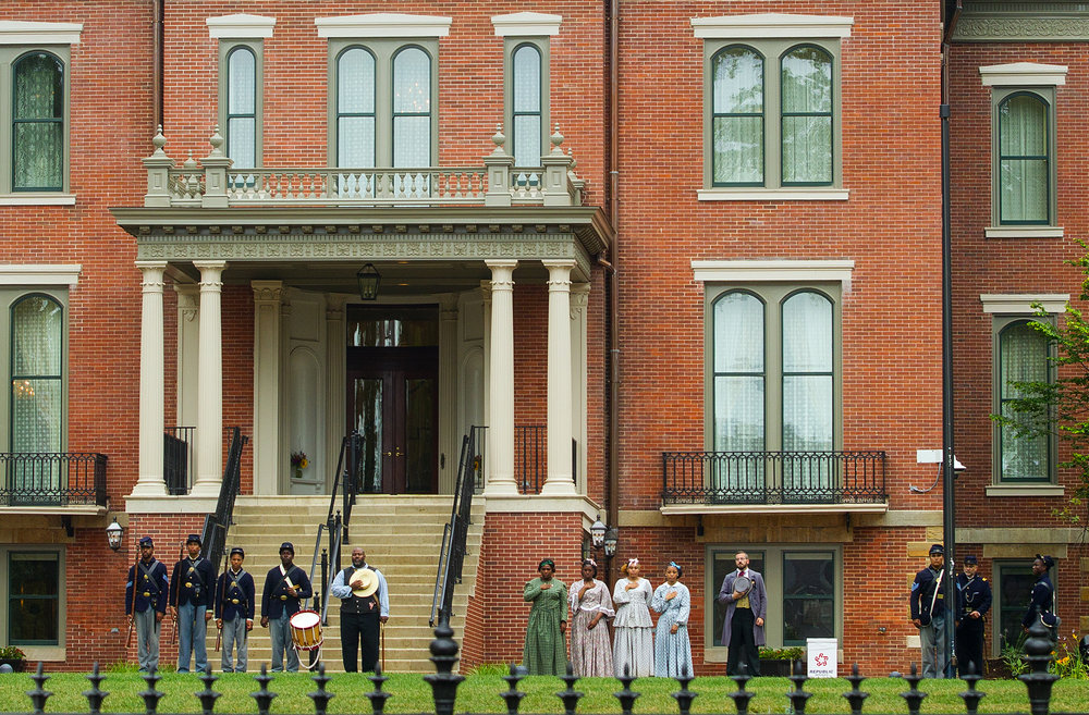 A group that portrays soldiers in the 29th Regiment, United States Colored Infantry and women from the Freedman's Lady's Aid Society, wait to raise the flag at the grand reopening of the Illinois GovernorÕs Mansion on East Jackson Street in Springfield, Ill., Saturday, July 14, 2018. [Ted Schurter/The State Journal-Register]
