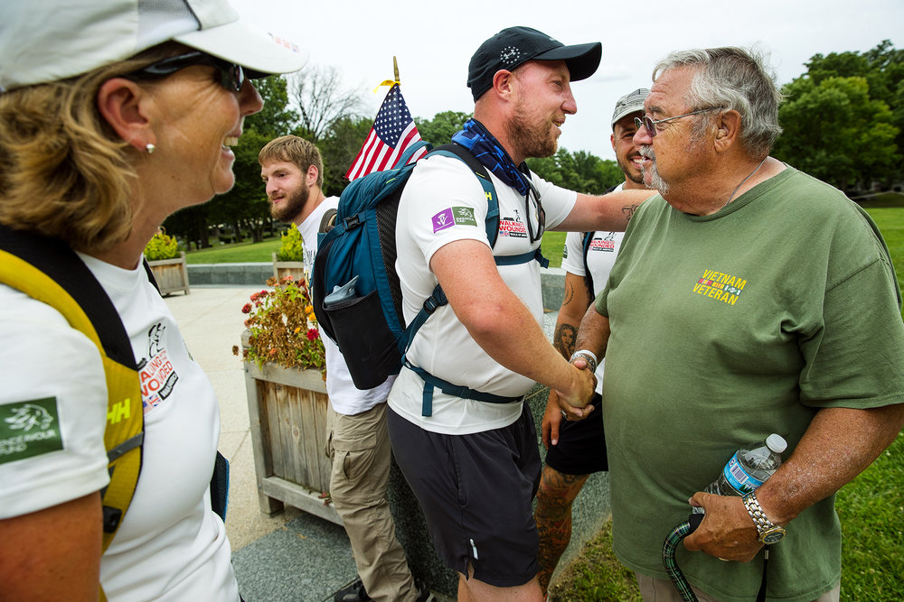 British Army veteran Kev Carr greets Marine Corps veteran Pete Rafferty after arriving at Lincoln's Tomb with five other members of The Walk Of America, a 1,000 mile walk to raise money and awareness of soldiers' physical recovery and mental health, Thursday, July 26, 2018. The six wounded veterans, three from the U.S. and three from England, met Rafferty when he was hiking with Boy Scout Troop 1 in Yellowstone National Park earlier this month.Rafferty's group encouraged them to hike Lincoln's Trail, the same path used during the annual Boy Scout Pilgrimage. The group hiked from New Salem to the tomb. [Ted Schurter/The State Journal-Register]