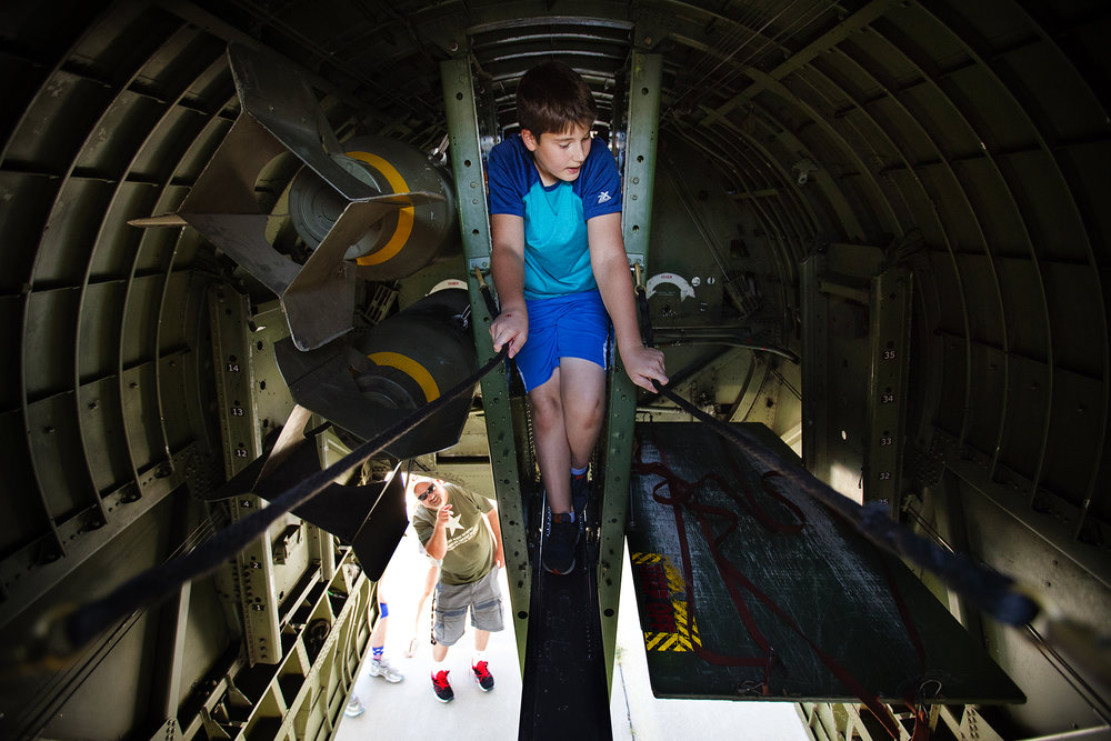 Nicolas Titone climbs through the belly of a WWII vintage Boeing B-17 Flying Fortress during the Wings of Freedom Tour stop at Capital Airport Monday, July 23, 2018. [Ted Schurter/The State Journal-Register]