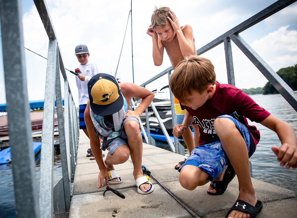 Alex Helen, 10, center, reacts as a bluegill flops around on the dock also startling William Coady, 10, left, who caught the fish, and Henry Pennell, 9, right, during a catch and release Fishing Derby on Lake Springfield at the Island Bay Yacht Club, Tuesday, July 24, 2018, in Springfield, Ill. [Justin L. Fowler/The State Journal-Register]