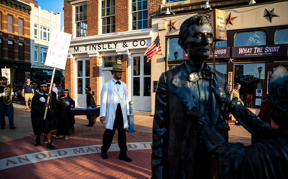Fritz Klein portraying Abraham Lincoln makes his way to the Old State Capitol passed the Lincoln-Herndon Law Offices during the Lincoln Wide Awake Parade, a re-enactment of an 1860 parade to support Abraham LincolnÕs presidential candidacy, as they march with the Wide Awakes to the Old State Capitol from the Lincoln Home, Saturday, Aug. 4, 2018, in Springfield, Ill. The Wide Awakes, who wore black caps and black hats when they marched, got their name from a small group of young self-named supporters who impressed Lincoln at a political rally, according to the Journal of American History. [Justin L. Fowler/The State Journal-Register]