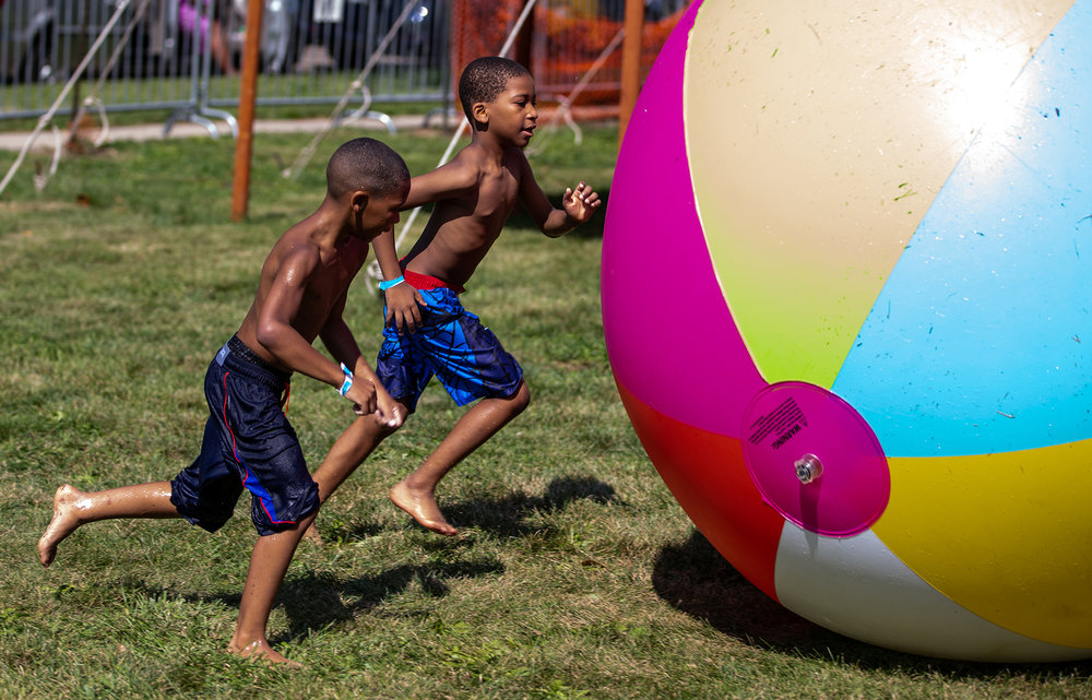 Semaj Felix, 9, left, and Demir Winston, 8, right, pilot a giant beach ball across the grass as they enjoy the H2o Park and bounce houses during the Blacks, Whites and Blues Festival the along 11th Street, Saturday, Aug. 4, 2018, in Springfield, Ill. [Justin L. Fowler/The State Journal-Register]