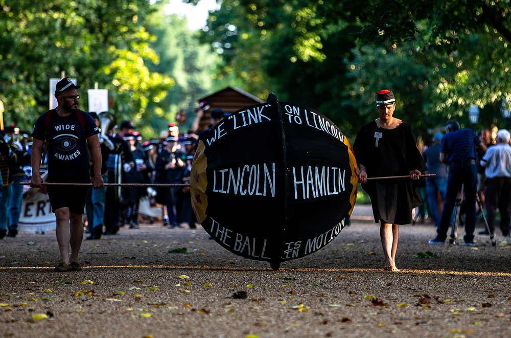 "Elliot Heilman, left, and John Paul Glover, right, pilot a massive replica of a campaign ball during the Lincoln Wide Awake Parade, a re-enactment of an 1860 parade to support Abraham Lincoln«s presidential candidacy, as they march with the Wide Awakes to the Old State Capitol from the Lincoln Home, Saturday, Aug. 4, 2018, in Springfield, Ill. The Wide Awakes, who wore black caps and black hats when they marched, got their name from a small group of young self-named supporters who impressed Lincoln at a political rally, according to the Journal of American History. ""The 1860 election was just the second time that the Republican Party had run a