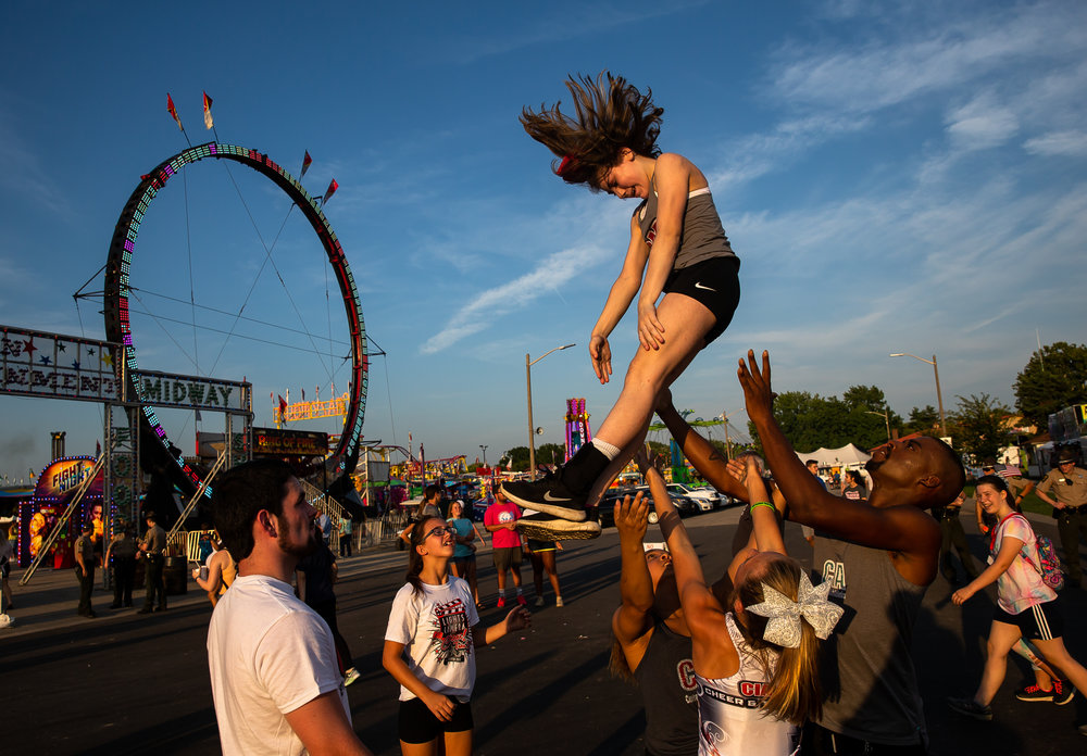 Chasie Moore soars into the are as she performs with the Central Illinois Athletics Cheer and Tumbling group during the Illinois State Fair Twilight Parade, Thursday, Aug. 9, 2018, in Springfield, Ill. [Justin L. Fowler/The State Journal-Register]