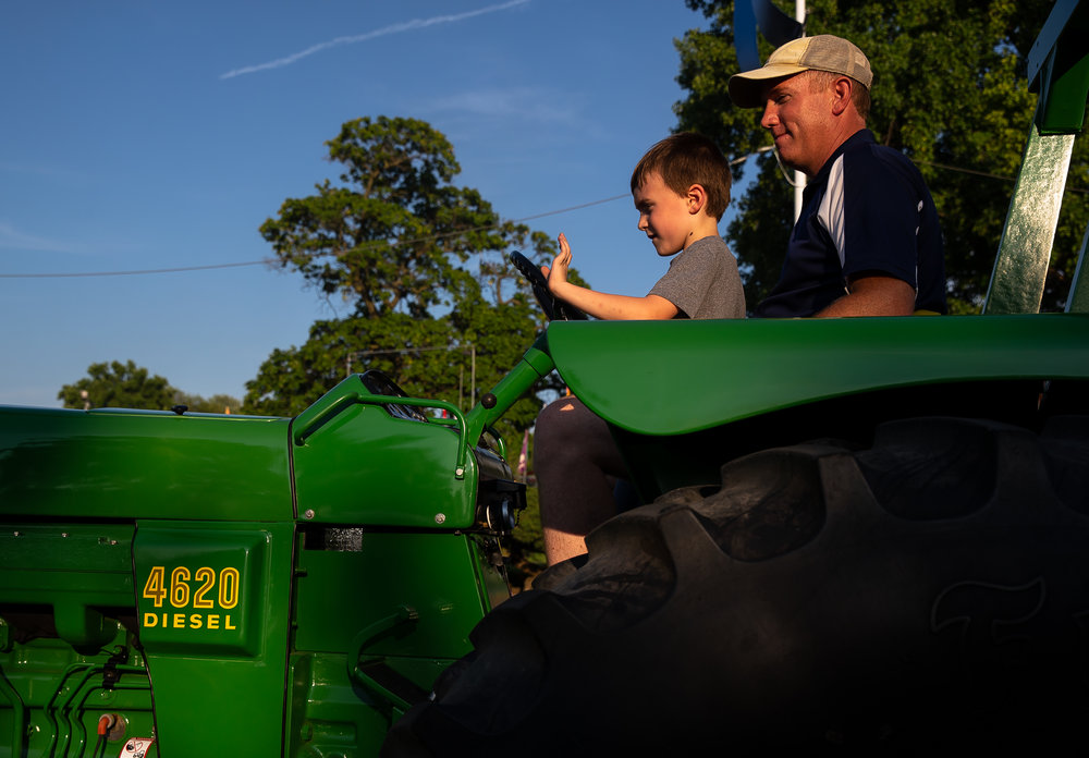 Brian Satorius guides his son, Ethan, as he pilots one of the antique tractors down Main Street during the Illinois State Fair Twilight Parade, Thursday, Aug. 9, 2018, in Springfield, Ill. [Justin L. Fowler/The State Journal-Register]