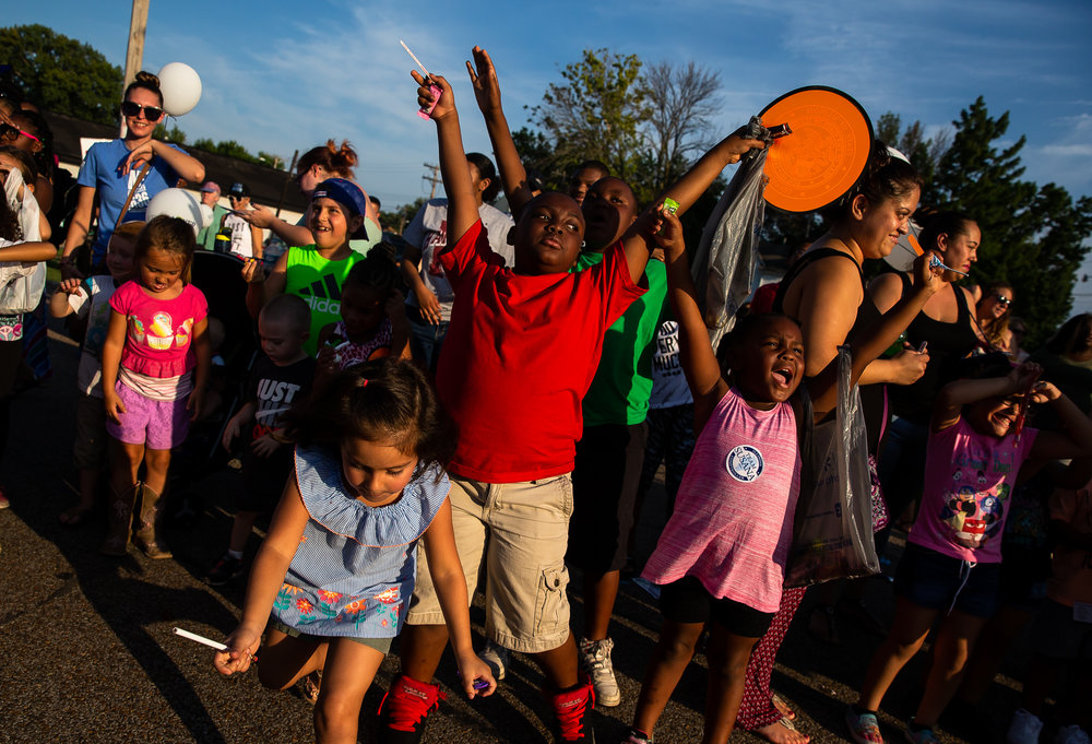 Elijah Brooks, 8, center joins in the call for candy as youth gather in the best spot for candy rewards outside the Main Gate during the Illinois State Fair Twilight Parade, Thursday, Aug. 9, 2018, in Springfield, Ill. [Justin L. Fowler/The State Journal-Register]