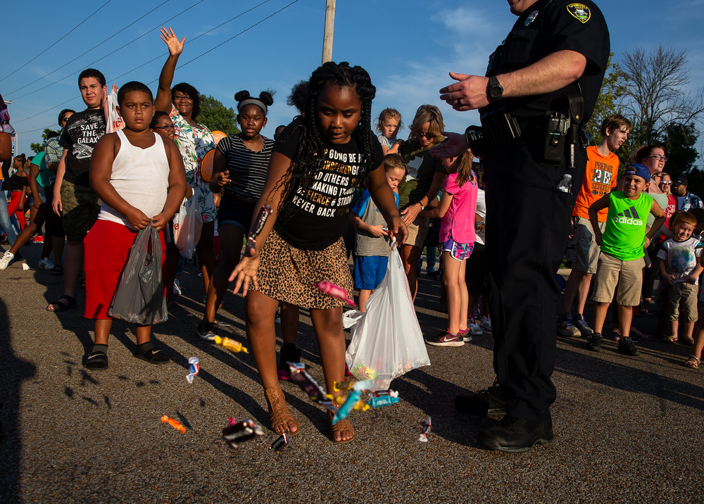The race for candy is on as children gather for the best spot as floats enter the Main Gate during the Illinois State Fair Twilight Parade, Thursday, Aug. 9, 2018, in Springfield, Ill. [Justin L. Fowler/The State Journal-Register]