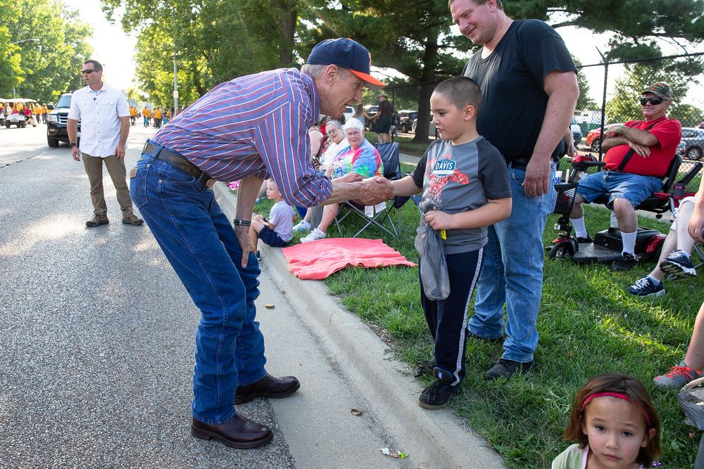 Illinois Governor Bruce Rauner shakes hands with Mathew Spain, 7, as he makes his way down the parade route on Sangamon Avenue during the Illinois State Fair Twilight Parade, Thursday, Aug. 9, 2018, in Springfield, Ill. [Justin L. Fowler/The State Journal-Register]