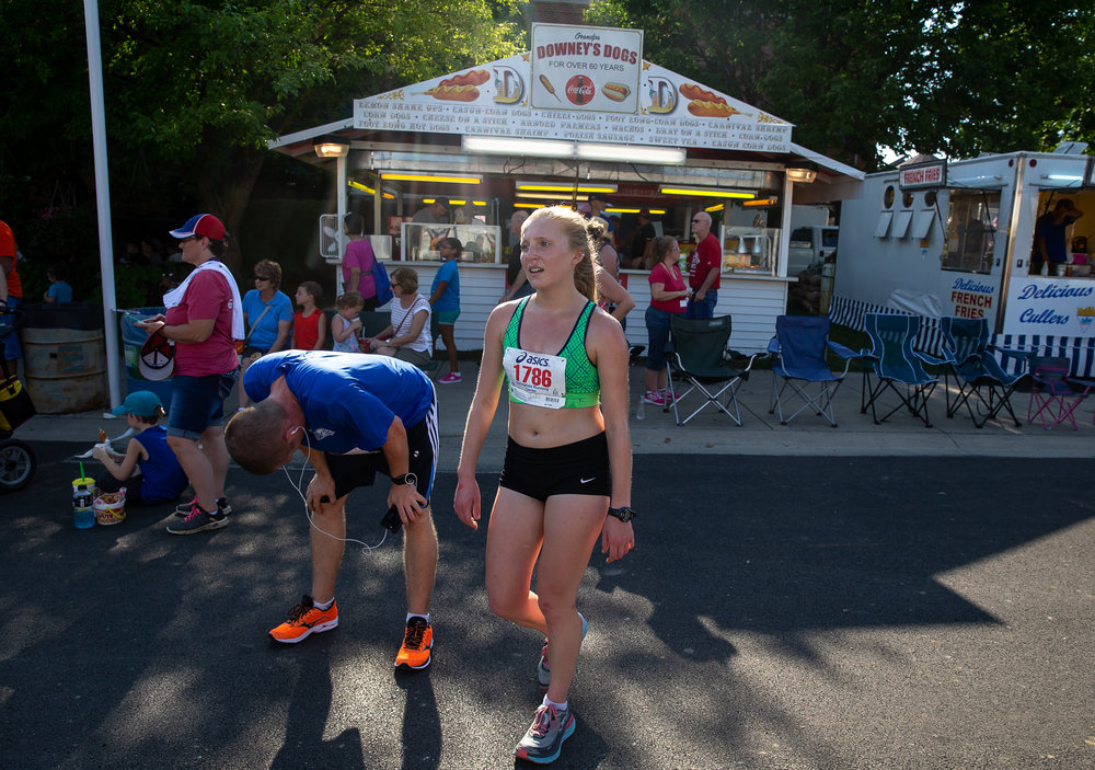 Adrienne Brauer catches her breath after crossing the finish line with a time of 12:08.6 to become the top female finisher in the Illinois State Fair Parade Run prior to the Illinois State Fair Twilight Parade, Thursday, Aug. 9, 2018, in Springfield, Ill. [Justin L. Fowler/The State Journal-Register]