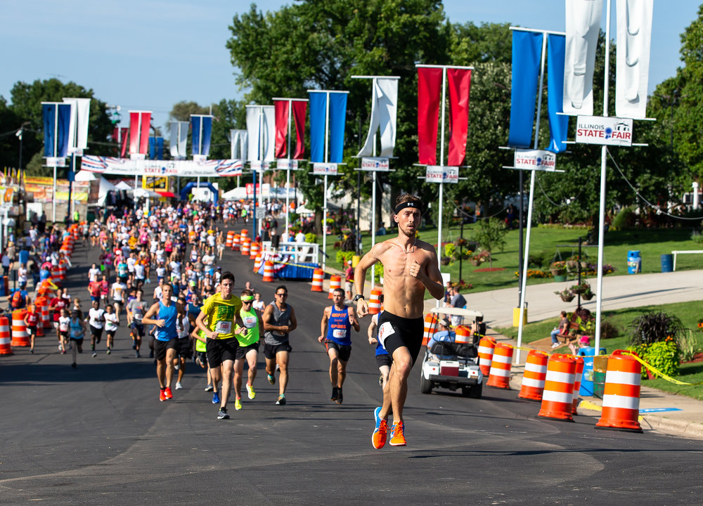 Daniel Plunkett breaks out to an early lead from the start of the Illinois State Fair Parade Run prior to the Illinois State Fair Twilight Parade, Thursday, Aug. 9, 2018, in Springfield, Ill. Plunkett was the overall and male winner of the race with a time of 9:50.9.  [Justin L. Fowler/The State Journal-Register]