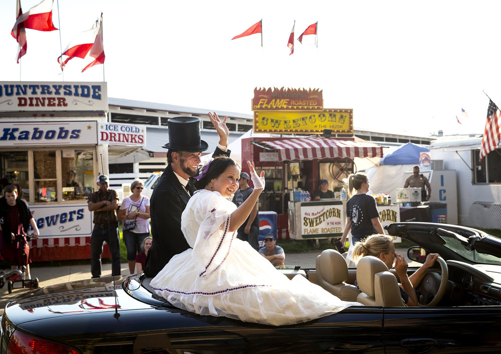 Frits Klein as Abraham Lincoln and Pam Brown at Mary Todd, ride through the fairgrounds during the Illinois State Fair Twilight Parade Thursday, Aug. 9, 2018 on the Illinois State Fairgrounds in Springfield, Ill. [Rich Saal/The State Journal-Register]