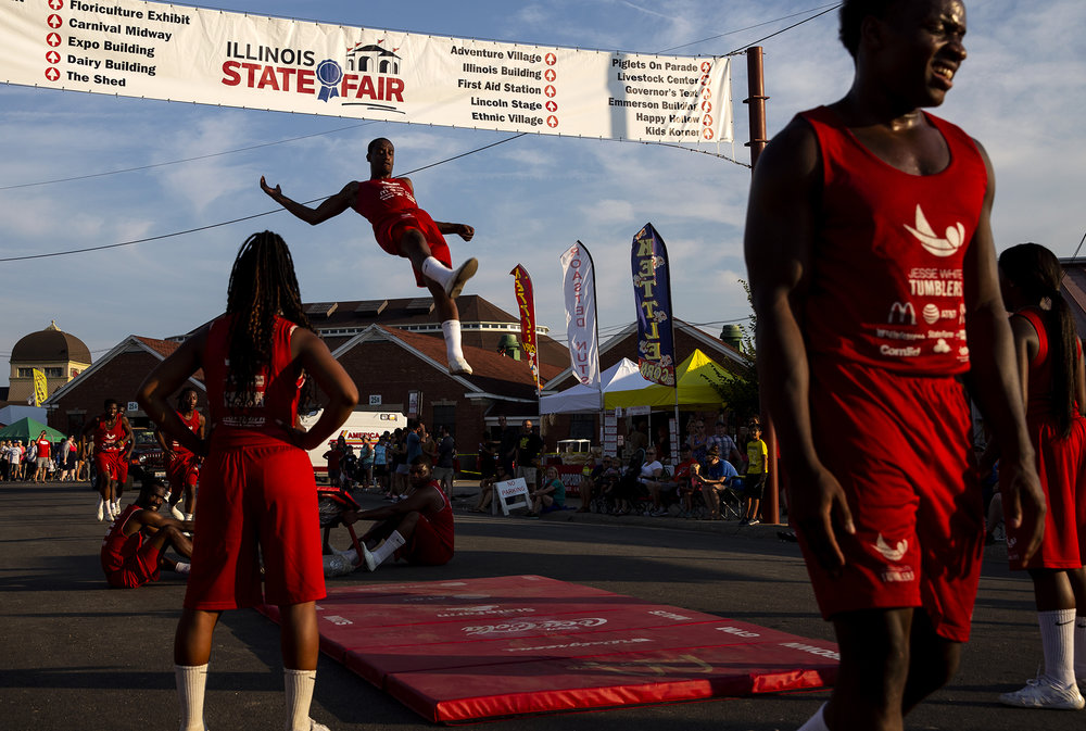 The Jesse White Tumblers perform along Grandstand Avenue during the Illinois State Fair Twilight Parade Thursday, Aug. 9, 2018 on the Illinois State Fairgrounds in Springfield, Ill. [Rich Saal/The State Journal-Register]