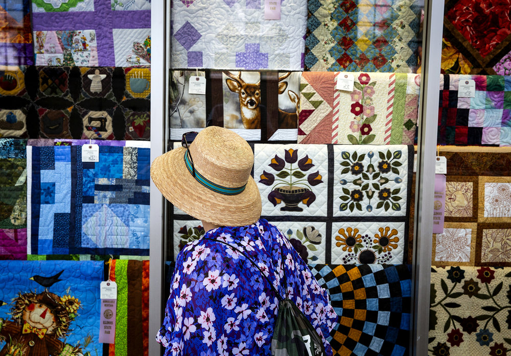 Marisa Denicolohann of Woodstock, views the winning quilts displayed in the Hobbies, Arts and Crafts building at the Illinois State Fair Saturday, Aug. 11, 2018 on the fairgrounds in Springfield, Ill. [Rich Saal/The State Journal-Register]