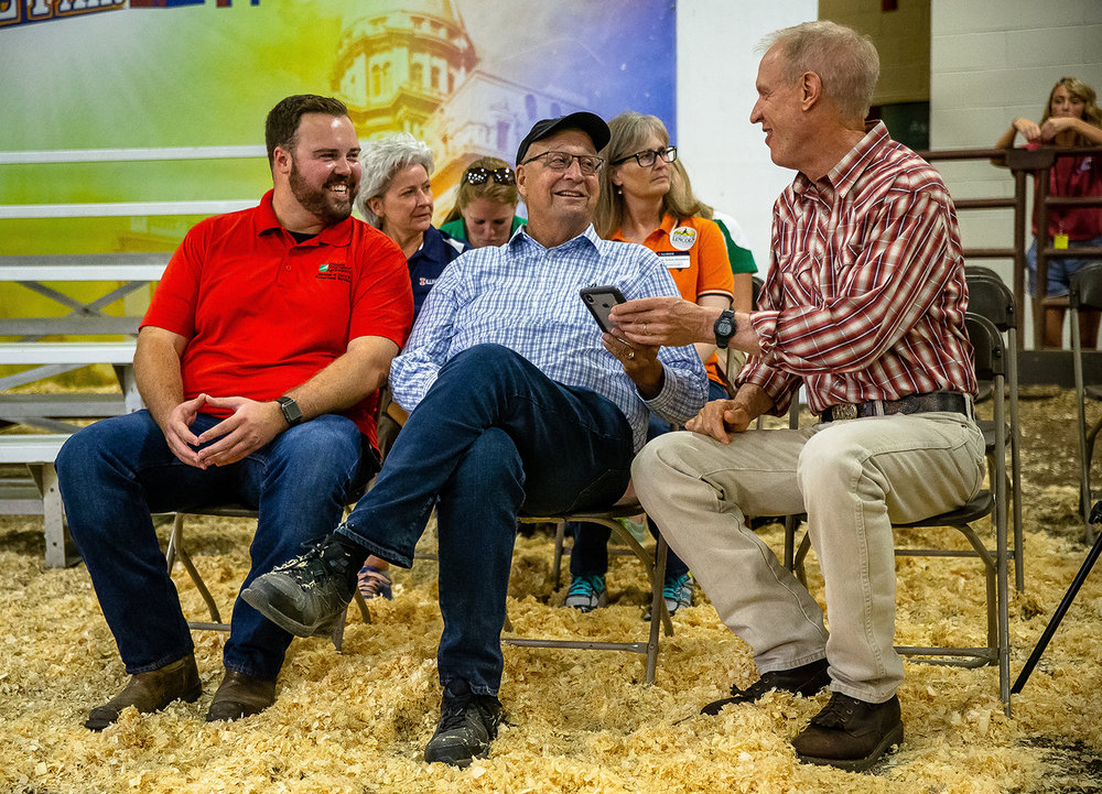 Illinois Governor Bruce Rauner, right, visits with Illinois Agriculture Director Raymond Poe, center, and Illinois State Fair Manager Luke Sailer, left, during the Parade of Champions at the Livestock Center during the Illinois State Fair at the Illinois State Fairgrounds, Saturday, Aug. 11, 2018, in Springfield, Ill. [Justin L. Fowler/The State Journal-Register]