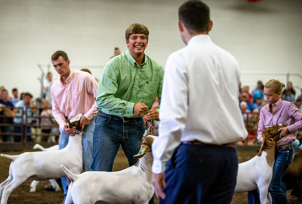 Chase Tomhave, 19, of Jacksonville, Ill., is all smiles as he wins Grand Champion meat goat wether during the Parade of Champions at the Livestock Center during the Illinois State Fair at the Illinois State Fairgrounds, Saturday, Aug. 11, 2018, in Springfield, Ill. [Justin L. Fowler/The State Journal-Register]