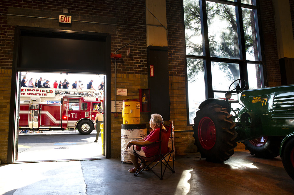 Judy Reed watches the Illinois State Fair Twilight Parade pass from a spot inside the grandstand and out of the sun Thursday, Aug. 9, 2018 on the Illinois State Fairgrounds in Springfield, Ill. [Rich Saal/The State Journal-Register]