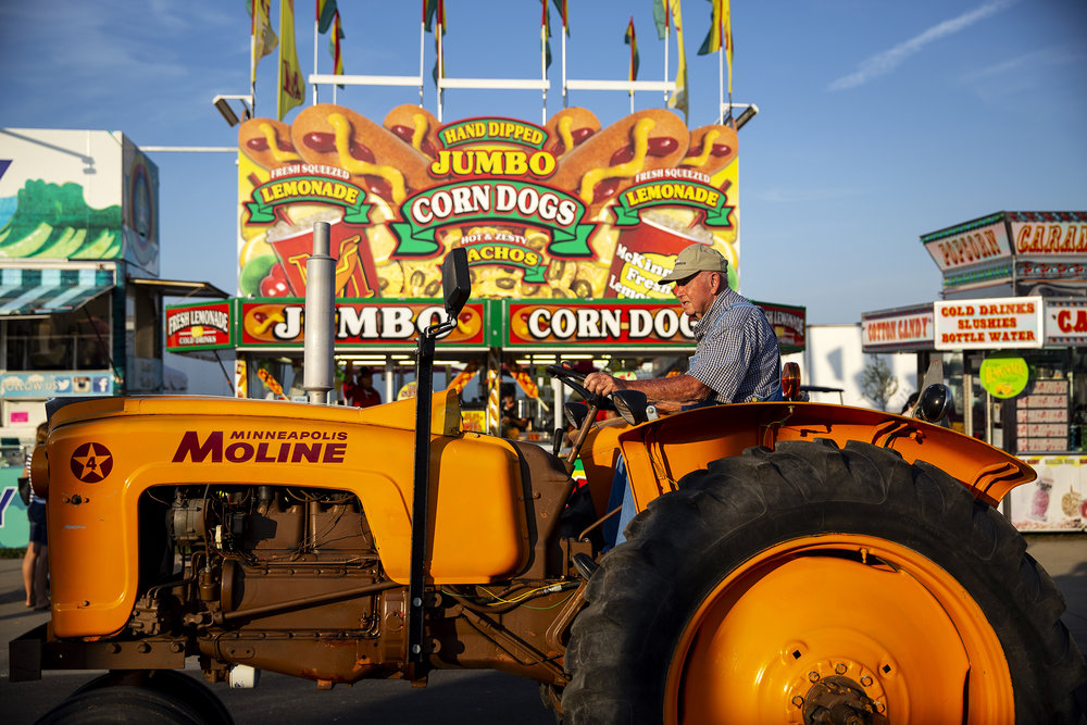 Edgar Robinson of Ashland drives his restored 1959 Minneapolis Moline tractor down Grandstand Avenue during the Illinois State Fair Twilight Parade Thursday, Aug. 9, 2018 on the Illinois State Fairgrounds in Springfield, Ill. [Rich Saal/The State Journal-Register]