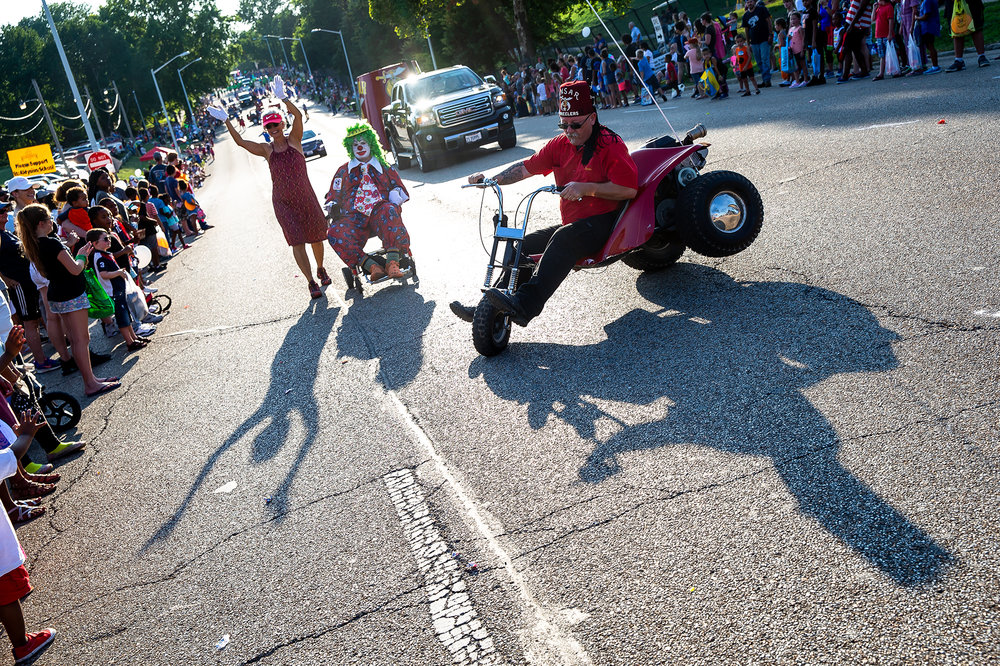 A rider with the Ansar Shrine 3 Wheelers pops up on two wheels as they perform along Sangamon Avenue while riding in the Illinois State Fair Twilight Parade, Thursday, Aug. 9, 2018, in Springfield, Ill. [Justin L. Fowler/The State Journal-Register]