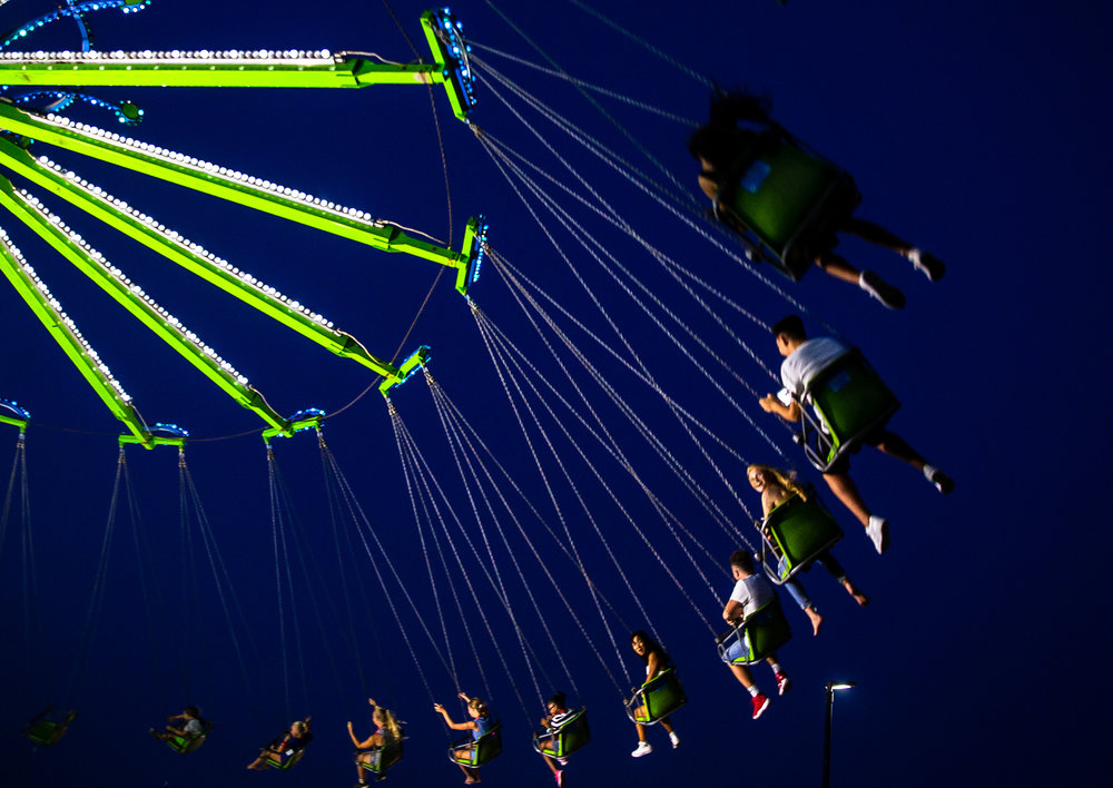 Youth go for a ride through the air on the YoYo chair swing in the Carnival Midway during the Illinois State Fair at the Illinois State Fairgrounds, Sunday, Aug. 12, 2018, in Springfield, Ill. [Justin L. Fowler/The State Journal-Register]