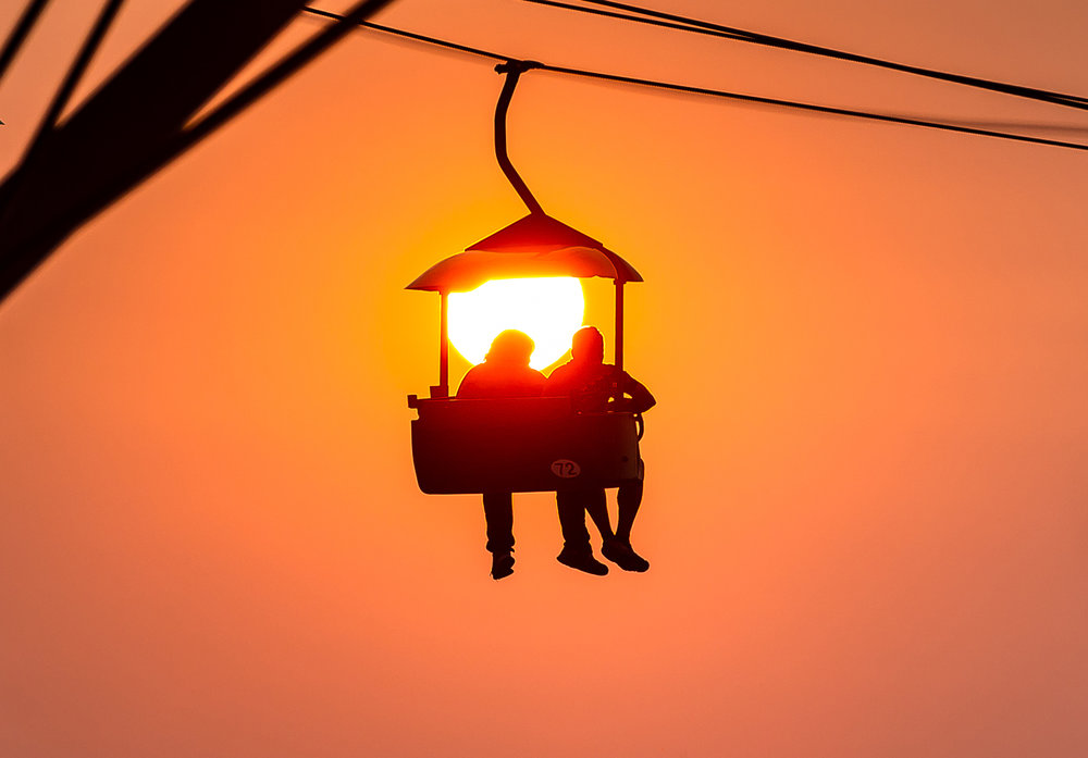 Fairgoers take in the setting sun from the Sky Glide as the first weekend comes to a close during the Illinois State Fair at the Illinois State Fairgrounds, Sunday, Aug. 12, 2018, in Springfield, Ill. [Justin L. Fowler/The State Journal-Register]