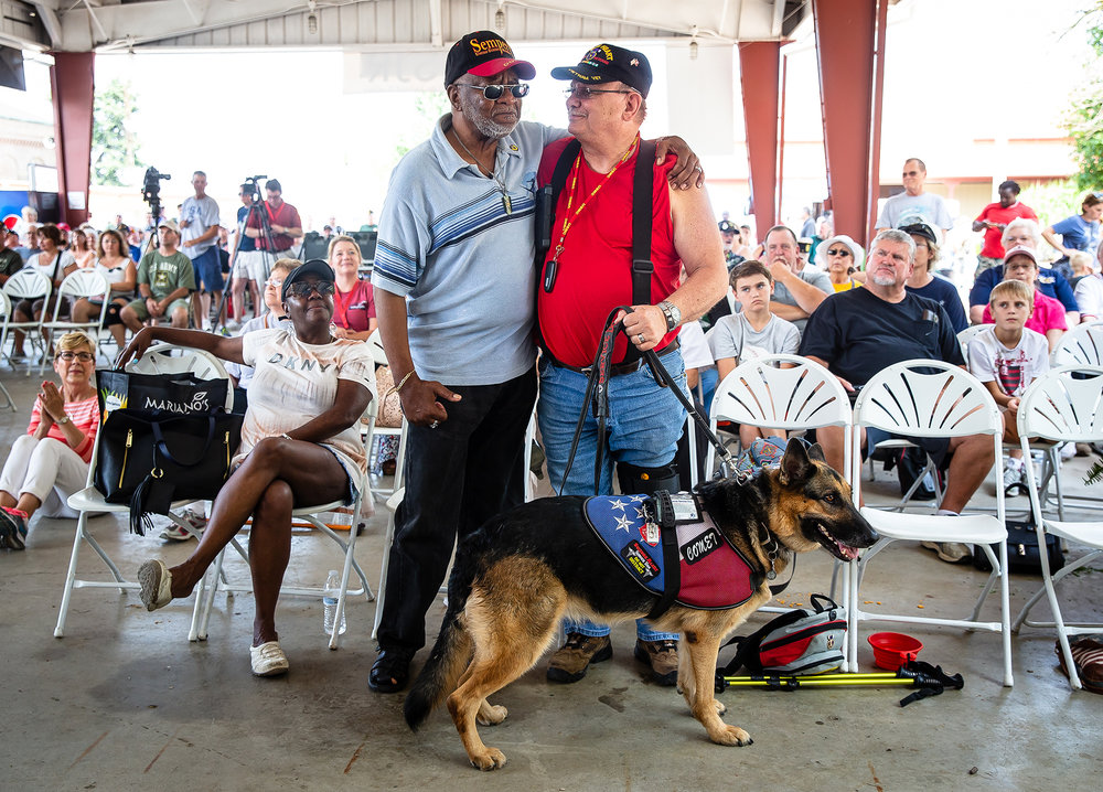 "Marine Corps Vietnam Veterans James T. Blue Sr., left, of Chicago, Ill., and Bradley Stephens, right, of Pana, Ill., along with Stephens' service dog Comet, hug each other as the Marines' Hymn is played as veterans from each branch of the military are honored with an armed forces medley during the Veterans Day program at the Illinois State Fair on the Lincoln Stage at the Illinois State Fairgrounds, Sunday, Aug. 12, 2018, in Springfield, Ill. Blue and Stephens both served in Vietnam, but never met each other while there, but have been life long friends since connecting in the 70s. ""We're not only friends we're brothers,"" said Stephens. [Justin L. Fowler/The State Journal-Register]"