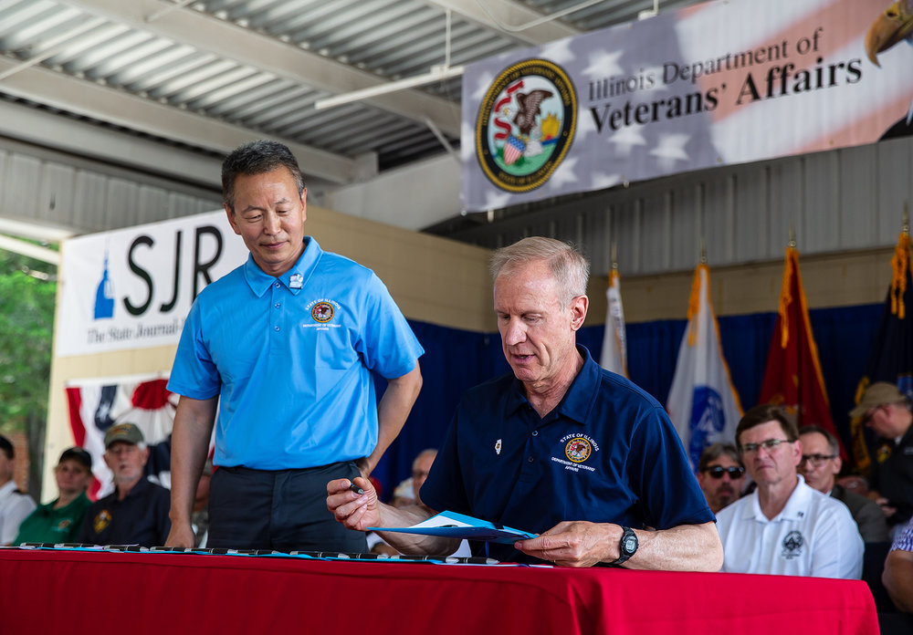 Illinois Governor Bruce Rauner signs multiple bills dealing with Veterans during the Veterans Day program at the Illinois State Fair on the Lincoln Stage at the Illinois State Fairgrounds, Sunday, Aug. 12, 2018, in Springfield, Ill. Rauner signed six bills at the main program aimed at helping veterans, including legislation proclaiming Nov. 4 the GI Bill of Rights Day; requiring health care providers to provide one free, complete copy of a patient's medical records if the patient is an indigent homeless veteran; expanding acceptable forms of proof needed to obtain a veteran's designation on identification cards; and allowing those who earned the Southeast Asia Service Medal during Operation Desert Storm to have the feat reflected on their license plates. [Justin L. Fowler/The State Journal-Register]