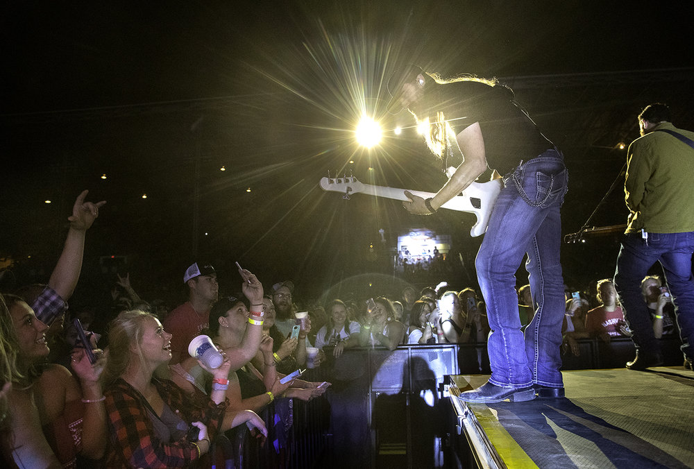 The bass player leans down toward the crowd as he performs with country artist Luke Combs at the Grandstand during the Illinois State Fair Tuesday, Aug. 14, 2018. [Ted Schurter/The State Journal-Register]