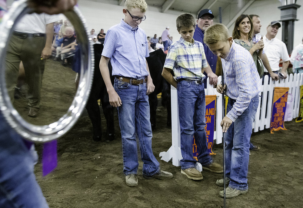 Chase Hummel, left, Adam Miller and Keegan Murphy scratch out a game of tic tac toe in the dirt as they wait for their animals to take center stage during the Governor's Sale of Champions at the Livestock Center at the Illinois State Fair Tuesday, Aug. 14, 2018. [Ted Schurter/The State Journal-Register]
