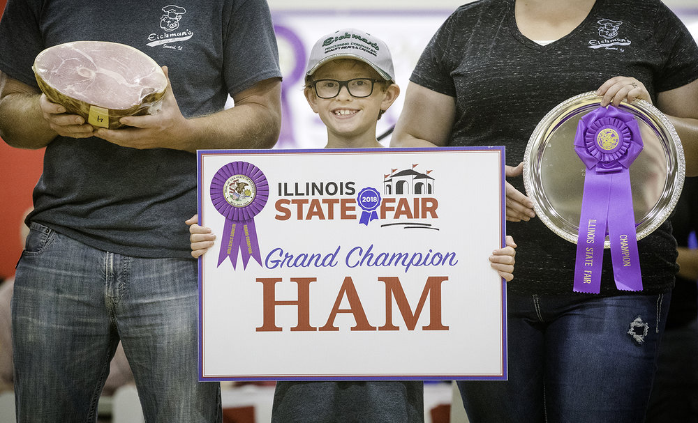 Ashton Eickman smiles as he holds up the Grand Champion Ham sign while flanked by his parents Tom and Katie during the Governor's Sale of Champions at the Illinois State Fair Tuesday, Aug. 14, 2018. According to his parents, Ashton helps out around the plant at Eickman's Processing, the family operation where the ham was made. [Ted Schurter/The State Journal-Register]