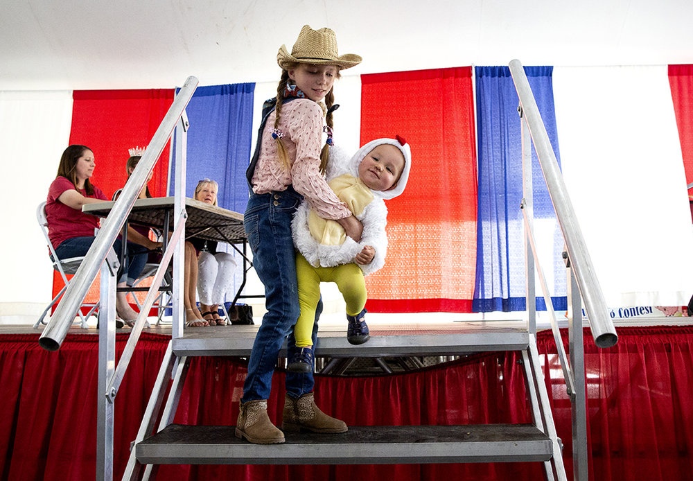 Lizzy Matzke, 8, helps her baby brother, Joey, 1, down the stairs after the two appeared in the Cutest Little Farmer contest in the Ag Tent at the Illinois State Fair Tuesday, Aug. 14, 2018 on the state fairgrounds in Springfield, Ill. [Rich Saal/The State Journal-Register]
