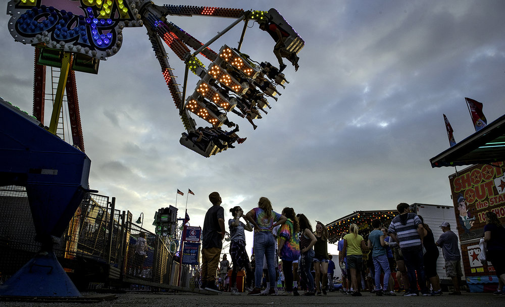 Fairgoers congregate under the Freak Out ride in the Carnival Midway at the Illinois State Fair Wednesday, Aug. 15, 2018. [Ted Schurter/The State Journal-Register]