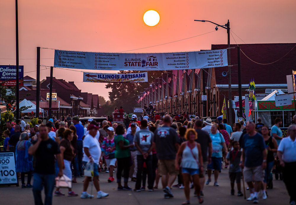 Fairgoers pack Central Avenue as the sun begins to set to finish out the first weekend during the Illinois State Fair at the Illinois State Fairgrounds, Sunday, Aug. 12, 2018, in Springfield, Ill. [Justin L. Fowler/The State Journal-Register]