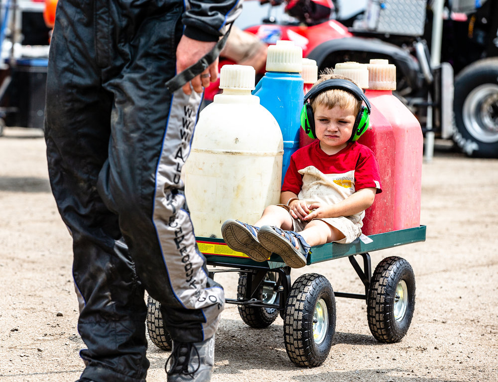 Ross Shepherd, 2, the son of USAC driver Neil Shepherd, hitches a ride on the card inside the pit area prior to the start of the USAC Silver Crown Bettenhausen 100 on the Springfield Mile during the Illinois State Fair at the Illinois State Fairgrounds, Saturday, Aug. 18, 2018, in Springfield, Ill. [Justin L. Fowler/The State Journal-Register]