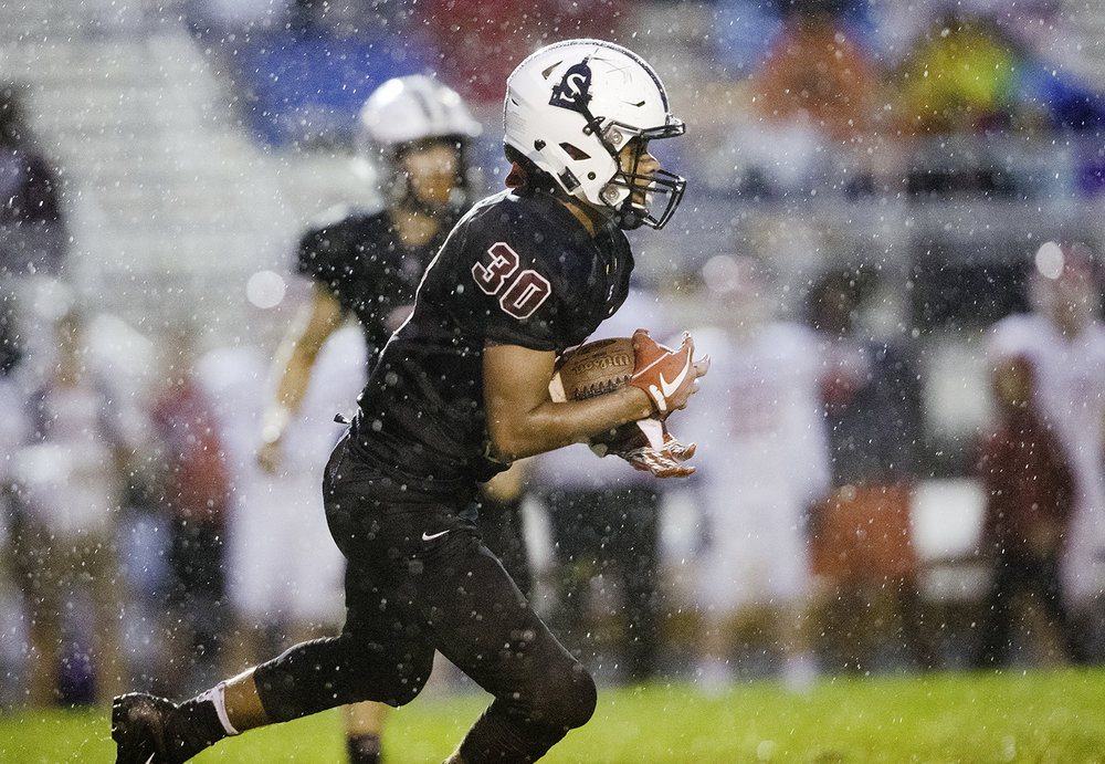 Springfield's Qa'ron Hawkins receives a kick from Glenwood at Memorial Stadium Friday, Sept. 7, 2018. [Ted Schurter/The State Journal-Register]