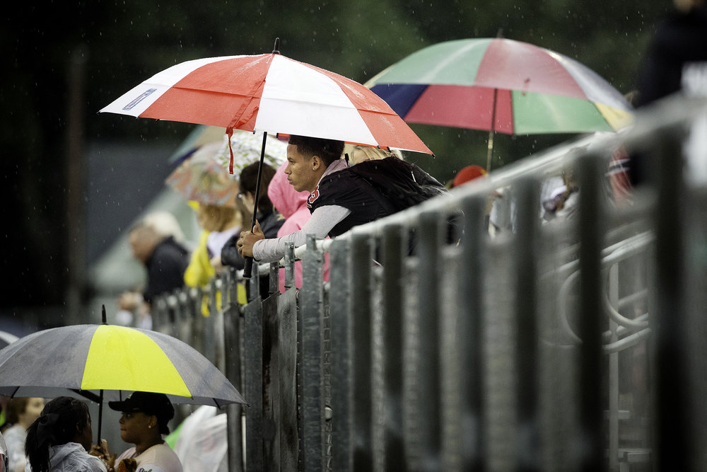 Springfield fans wait under umbrellas for kick-off against Glenwood on a rainy night at Memorial Stadium Friday, Sept. 7, 2018. [Ted Schurter/The State Journal-Register]