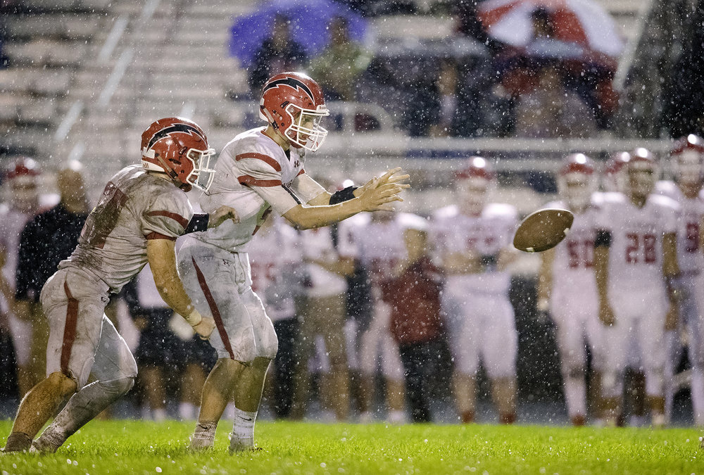 Glenwood's Luke Lehnen takes a snap as Austin Schiff prepares to take a hund off at Memorial Stadium Friday, Sept. 7, 2018. [Ted Schurter/The State Journal-Register]