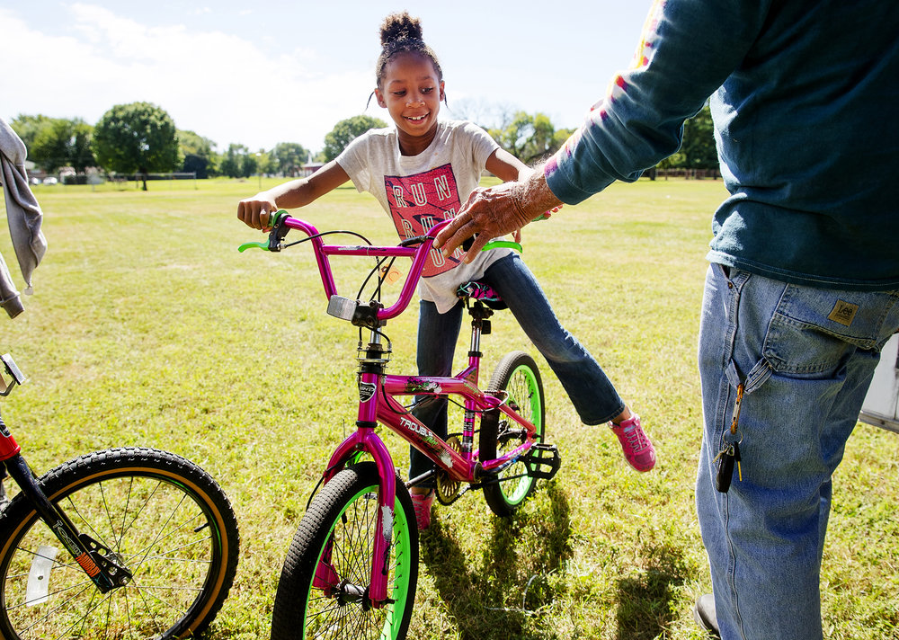 Kierra Evans smiles as she looks at the new bike she picked out after winning a raffle at The Outlet's fifth annual Bridging the Gap BBQ at Jaycee Park Saturday, Sept. 22, 2018. Evans said she choose the bike because she liked the pretty color. The Outlet established the free event that featured food, games, music and more with the hope of  bring members of the community together with police and first responders to develop a more familiar and trusting relationship in a fun relaxed environment. [Ted Schurter/The State Journal-Register]