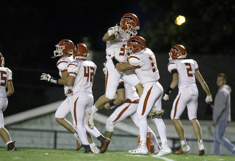 The Titans celebrate after getting a safety against Decatur MacArthur at Decatur MacArthur High School Friday, Sept. 28, 2018. [Ted Schurter/The State Journal-Register]