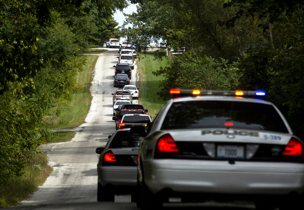 Springfield Police officers, retired members of the department and a few officers from other agencies, home delivered a gesture of support for a former colleague who is battling cancer when they drove in procession past his home north of Springfield Wednesday, Sept. 26, 2018. The retired officer is a 32 year veteran of the department. About 50 vehicles participated, briefly turning on their sirens and lights when they turned around in the circle driveway. [Rich Saal/The State Journal-Register]