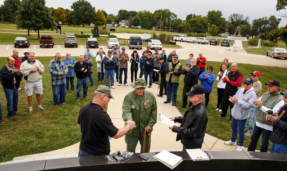 Mike Dahlkamp, left, hands Charles Spencer a commemorative pin during a brief ceremony at the Vietnam War Memorial in Oak Ridge Cemetery Saturday, Sept. 29, 2018. The gathering was for members of the Springfield High Class of 1968 who were Vietnam veterans. Jim Long is at right. [Ted Schurter/The State Journal-Register]