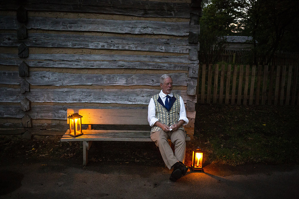 Harl Jones waits outside Dr. John Allen's home and office for visitors at the start of the annual candlelight walk through Lincoln's New Salem State Historic Site Friday, Oct. 5, 2018, in Petersburg, Ill. [Rich Saal/The State Journal-Register]