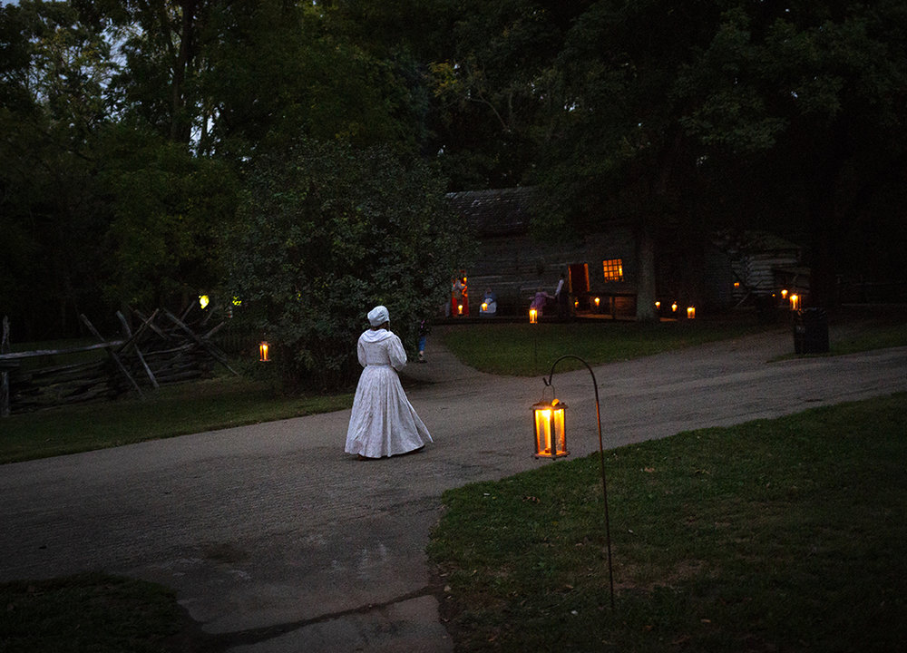 A volunteer makers her way to the Rutledge Tavern during the annual candlelight walk through Lincoln's New Salem State Historic Site Friday, Oct. 5, 2018, in Petersburg, Ill. [Rich Saal/The State Journal-Register]