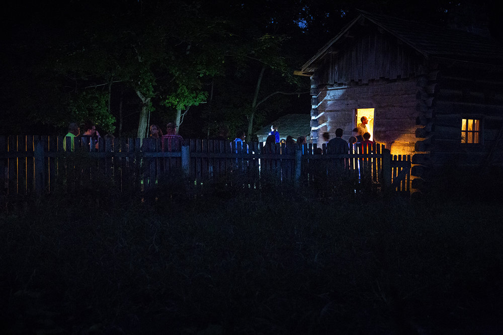 Visitors line up to see one of the log buildings in Lincoln's New Salem State Historic Site during their annual candlelight walk Friday, Oct. 5, 2018, in Petersburg, Ill. [Rich Saal/The State Journal-Register]